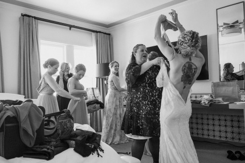 Wedding Prep Photographer | The bride gets help from her family and friends as she puts her wedding dress on.