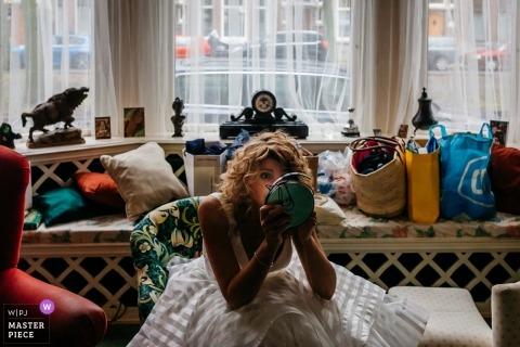 Panna młoda Den Haag używa lusterka do makijażu przed ceremonią ślubną
