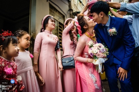 Vietnam Cantho wedding day rituals - Surprised faces of the kids to the couple kissing outside