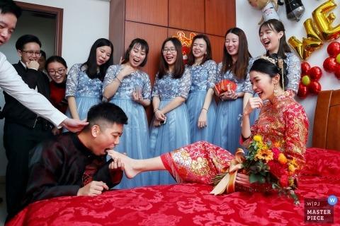 Photographie de mariage de Chine Zhuhai - la mariée colle le pied dans la bouche du marié à la réception du mariage