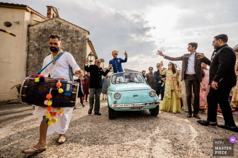 Hilton la Bagnaia, Siena wedding photographer - Indian wedding in Tuscany streets with the groom standing in a convertible car