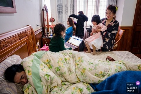 Ho Chi Minh wedding photos - Getting Ready with kids and a man sleeping on the bed