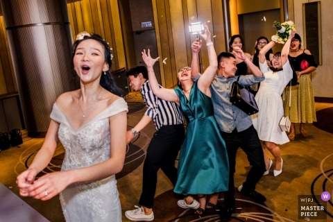 Ho Chi Minh wedding reception photography - the bride tosses her bouquet of flowers