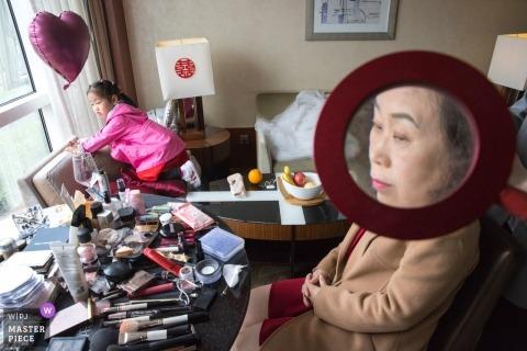 fotografia ślubna Pekinu - Kobieta powiększona w szkle do makijażu