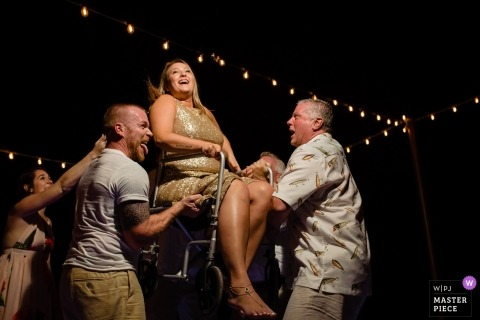 Cozumel, Mexico wedding photographer for Secrets Aura -wheelchair bridesmaid gets lifted by men on the dance floor