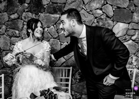Cazorla, Spanien Hochzeitsphotographie der Braut, die den Bräutigamkuchen auf die Spitze einer Klinge einzieht