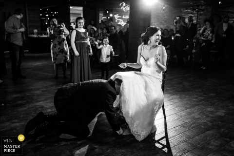 biagio evants wedding photography | garter dance about to begin the groom fishing the garter from under the dress of the seated bride