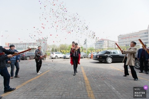TianJin actual day wedding photography - celebration with confetti cannons and the groom carrying his girl