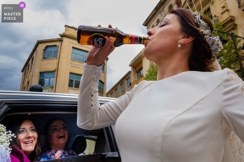 alcoy bride drinking a bottle of beer with bridesmaids watching from inside the car