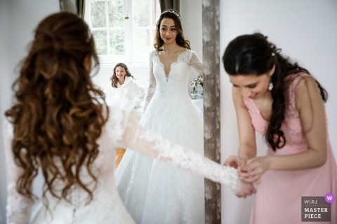 Lille - France wedding day photography | The dream of a little girl caught in the mirror of the bride putting on her dress