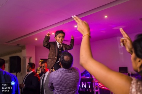 Froyle Park Country Estate, Hampshire, UK wedding photography | a small boy is lifted high above the guests on the dance floor at the reception