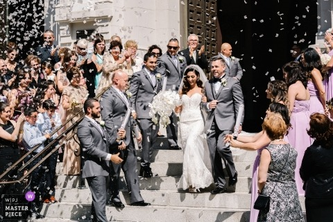 San Francisco wedding photograph of the bride and groom exiting the church under confetti