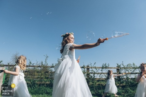 The Barns at Redcoats, Hitchin, Hertfordshire, UK wedding photographer | Flower girls playing with bubbles outside under blue skies