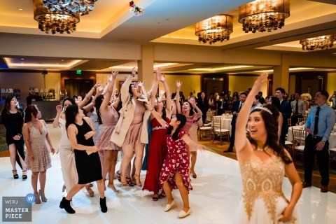 Garden Grove, CA wedding photographer | Who will be the next to catch the brides bouquet on the dance floor?