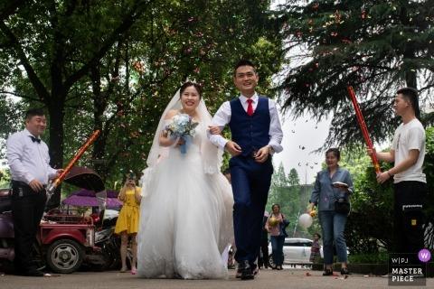 Zdjęcie ślubne Hunan panny młodej i pana młodego, chodzące pod armatkami konfetti na zewnątrz z drzewami