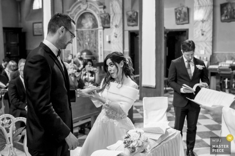 wedding ceremony photography Chiesa provincia lecco | the bride places the ring on the grooms finger during the ceremony