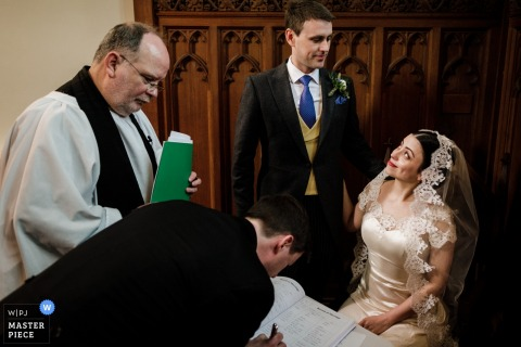 Clonabreany House, Ireland wedding photographer - Newlyweds exchange a look over signing of the marriage register