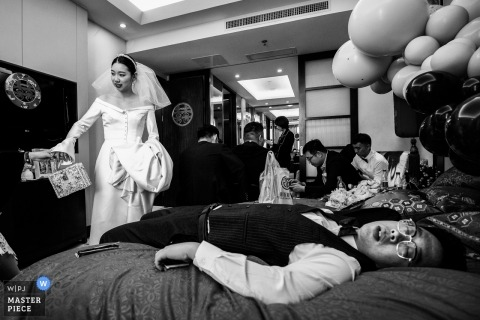 China bride Getting ready as a man sleeps on the bed before the ceremony