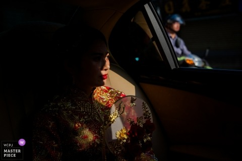 Fujian, China Wedding Photojournalism image of the bride in sunlight in the back of a car as a motor bike passes by