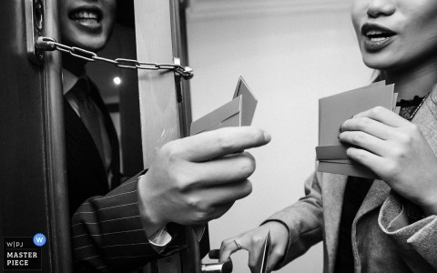 Quanzhou Hotel getting ready wedding photography | The groom is giving red envelopes through the locked door