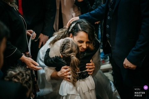 San Giovanni Battista (Giulianello LT) wedding photography | the Happy bride hugs a young girl