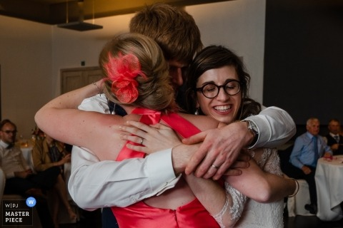 De Barrier Houthalen wedding photography - Triple hug at the reception party!