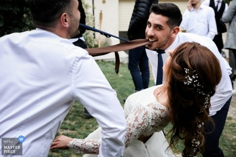 Wedding photographer for Paris - France - Reception limbo for the bride With men clenching ties in their teeth