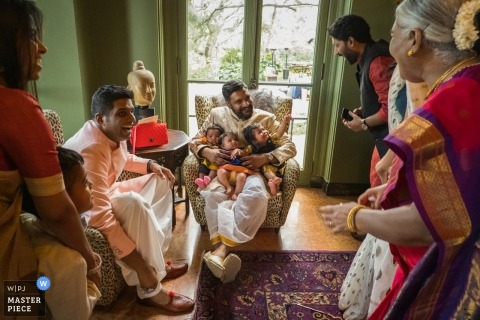 The Paramour Estate - wedding photography of groom holding three babies, celebrating his marriage with his family.