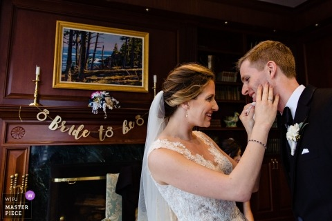 Point Lookout wedding photography | A bride cleans makeup off of her groom's face.