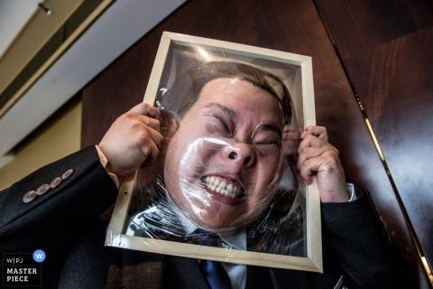 Gość bierze udział w grze, rozbijając twarz na plastiku na tym ślubie w Pekinie na tym zdjęciu autorstwa chińskiego fotografa ślubnego.