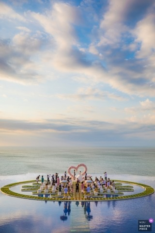 Photo of the ceremony on Fantasy Island in Bali with blue skies and clear water framing the wedding by a Zhejiang wedding photographer.