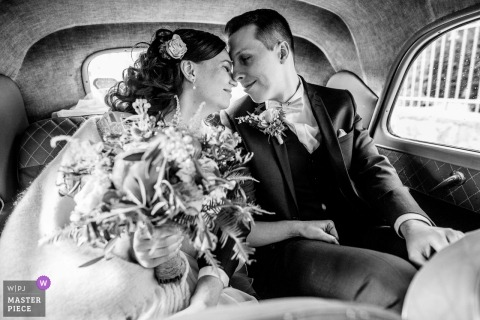 Black and White photo of the bride and groom having a quiet moment alone in the backseat of the car