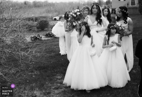 Black and White photograph of the bride with her bridesmaids and flower girls walking to the ceremoy site at Strathmere Ottawa Canada