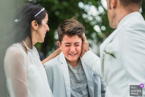 The bride and groom comfort a young man who gets emotional during the ceremony in this photo by a Paris, France wedding photographer.