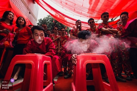 Image of men playing traditional Chinese wedding event of blowing flour.