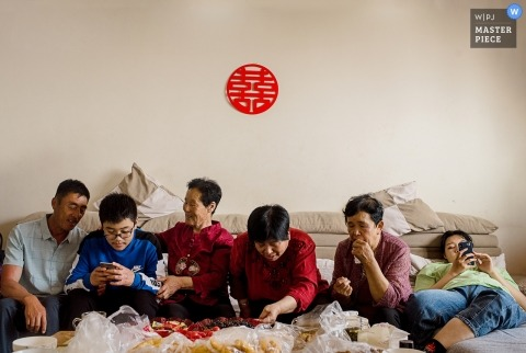 Guests sit and wait for the ceremony to begin in Shandong in this photo by a China wedding photographer.