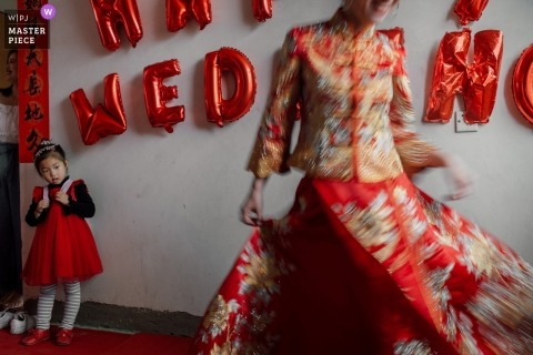 The bride twirls in her red wedding gown as a young girl watches in this photo by a Fujian, China wedding photographer.