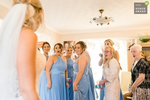 Bride walks in to reveal her wedding dress to her bridesmaids and grandparents