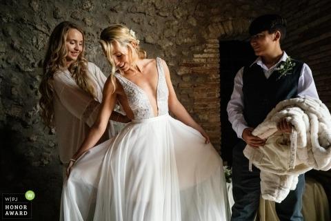Die Braut arrangiert das Kleid vor der Zeremonie im Castello Savelli Torlonia