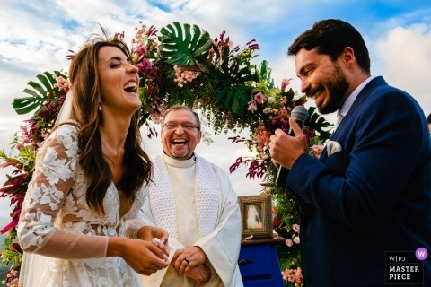 The bride and groom laugh at the altar during their outdoor ceremony at Vila Relicario in this photo by a Brazil wedding photographer.