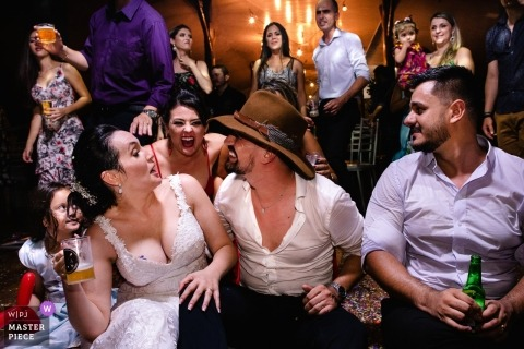 Photo of the bride and groom drinking with their friends during the reception in Pousada Avalon by a Brazil wedding photographer.