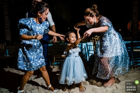 A dancing image of a young girl at a wedding on the sands of Nha Trang, Vietnam.