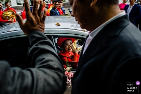 Ho Chi Minh family members wave goodbye to the bride as she leaves in a car.