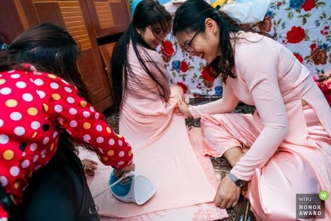 Last minute ironing on wedding day dresses before the ceremony in Ho Chi Minh.