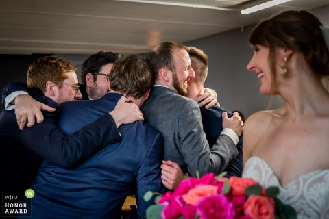 Groom receives a congratulatory group hug from his friends at the wedding.