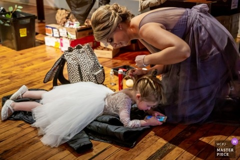 The flower girl lays on the floor getting her hair done at the Chicago-Bridgeport Art Center in this photo by a Chicago, IL wedding photographer.