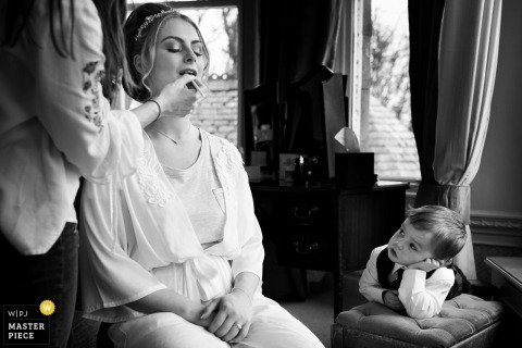 Black and white photo of a young boy watching as the bride gets her makeup done in Lake District by an England wedding photographer.