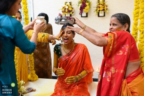 This photograph was made during the traditional bride making ceremony at her home. First the ladies of the house apply turmeric on her and then bathe her in Bangalore, India