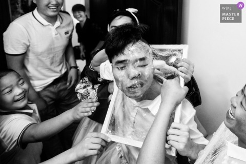 Black and white wedding photojournalism with guests molding a plastic frame around young man's face in Fujian, China.