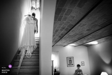 Czarno-białe zdjęcie kobiety niosącej suknię ślubną panny młodej na górze nad jej ramieniem w Marche autorstwa fotografa ślubnego z Włoch.